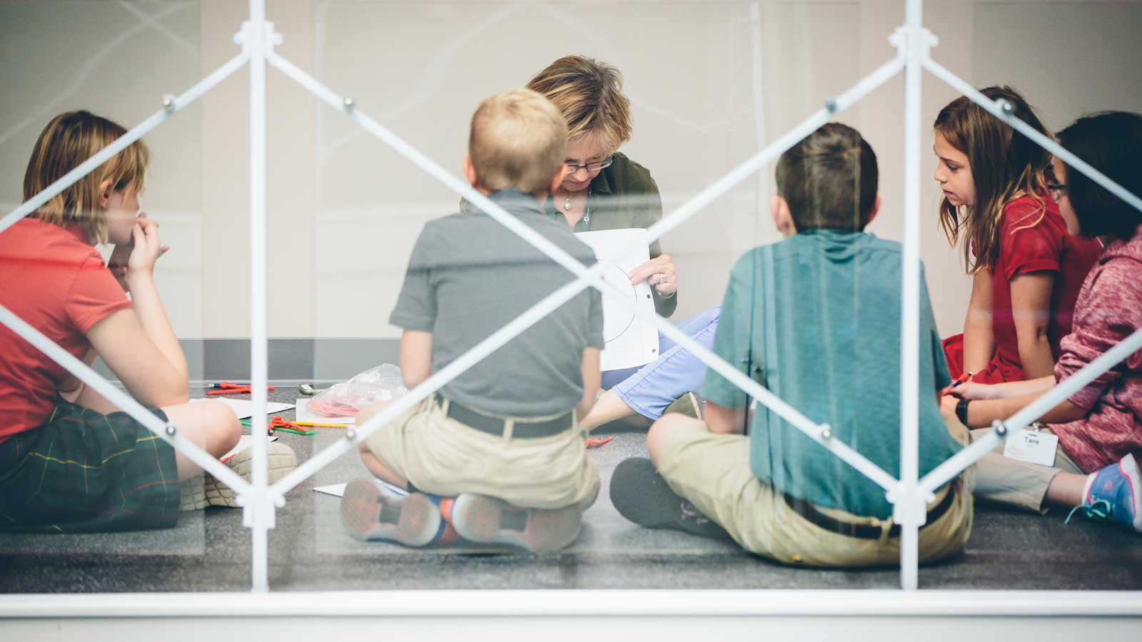 Students sitting with a teacher near a metal railing