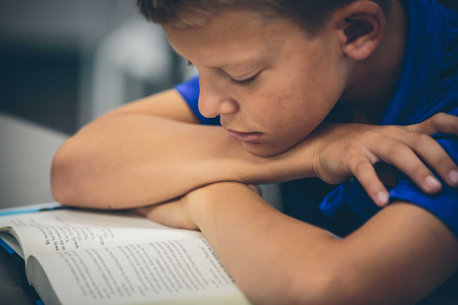 Kid with arms crossed reading a book