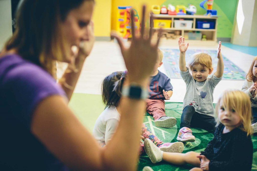 Preschool teacher with hands raised