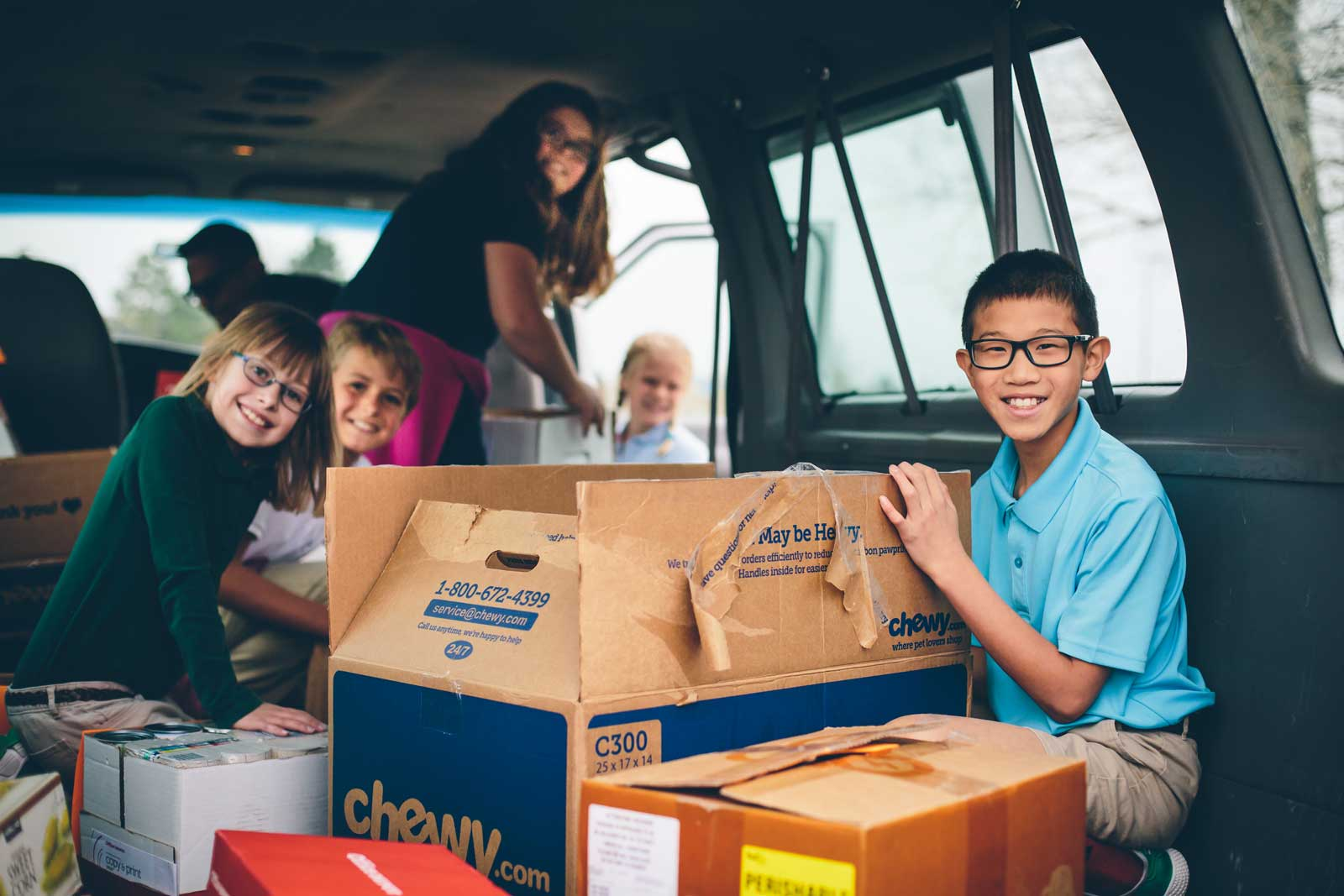 Kids loading a van with donated food items