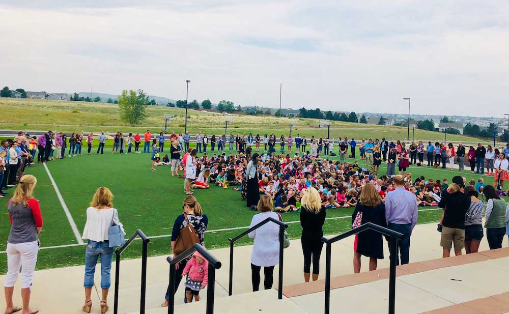 A large circle of praying parents surrounds dozens of children on an athletic field